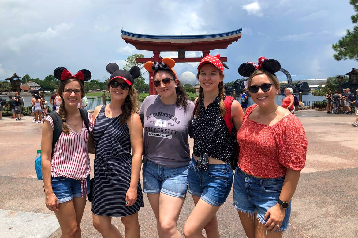 Five Caucasian women stand in a row wearing Mickey and Minnie ears near the Tori gat in the Japan pavilion at Epcot.