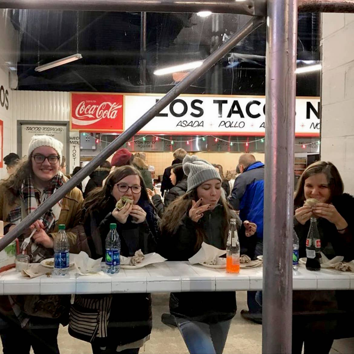 Four caucasian women wearing winter apparel are seated at a countertop at 'Los Tacos' in New York City.