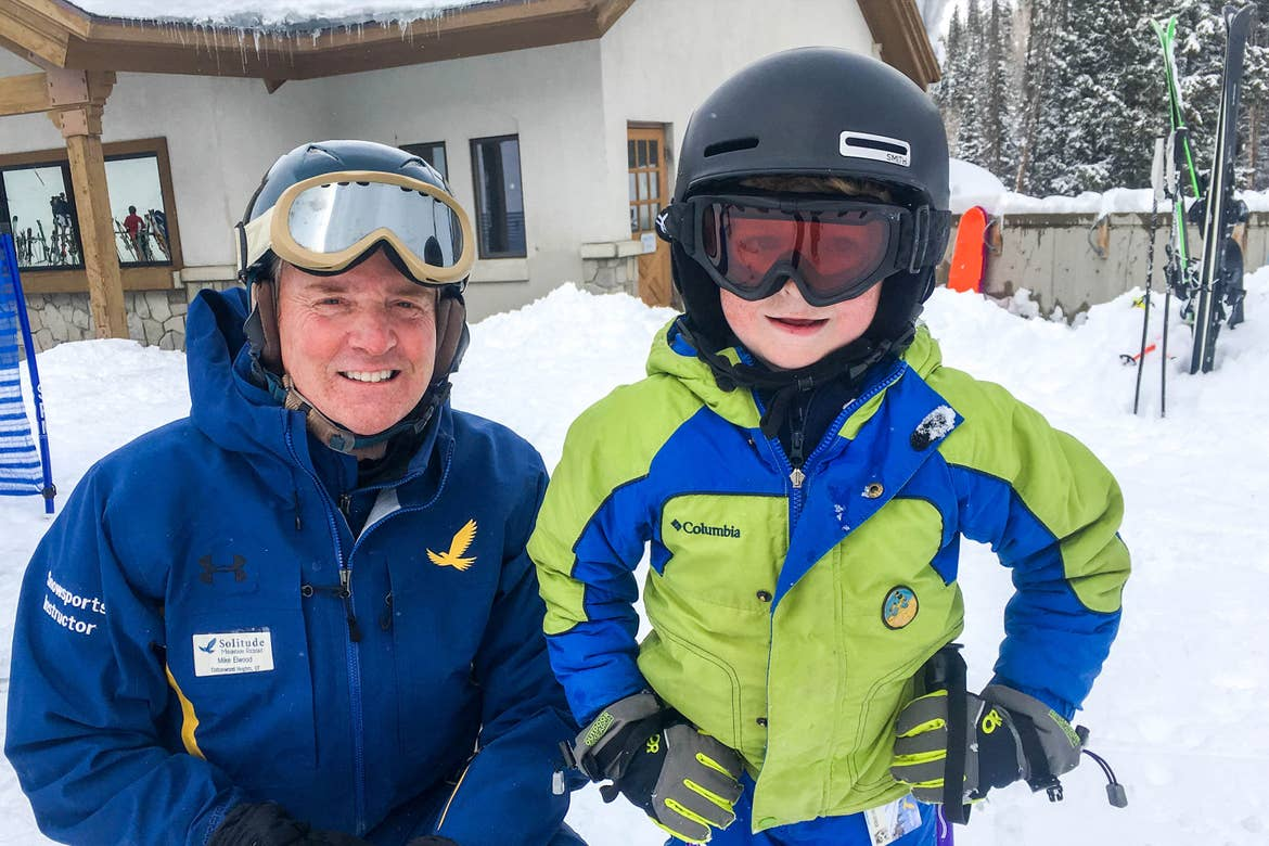 Jessica's son stands next to a Resort Employee wearing their winter and skiing gear.