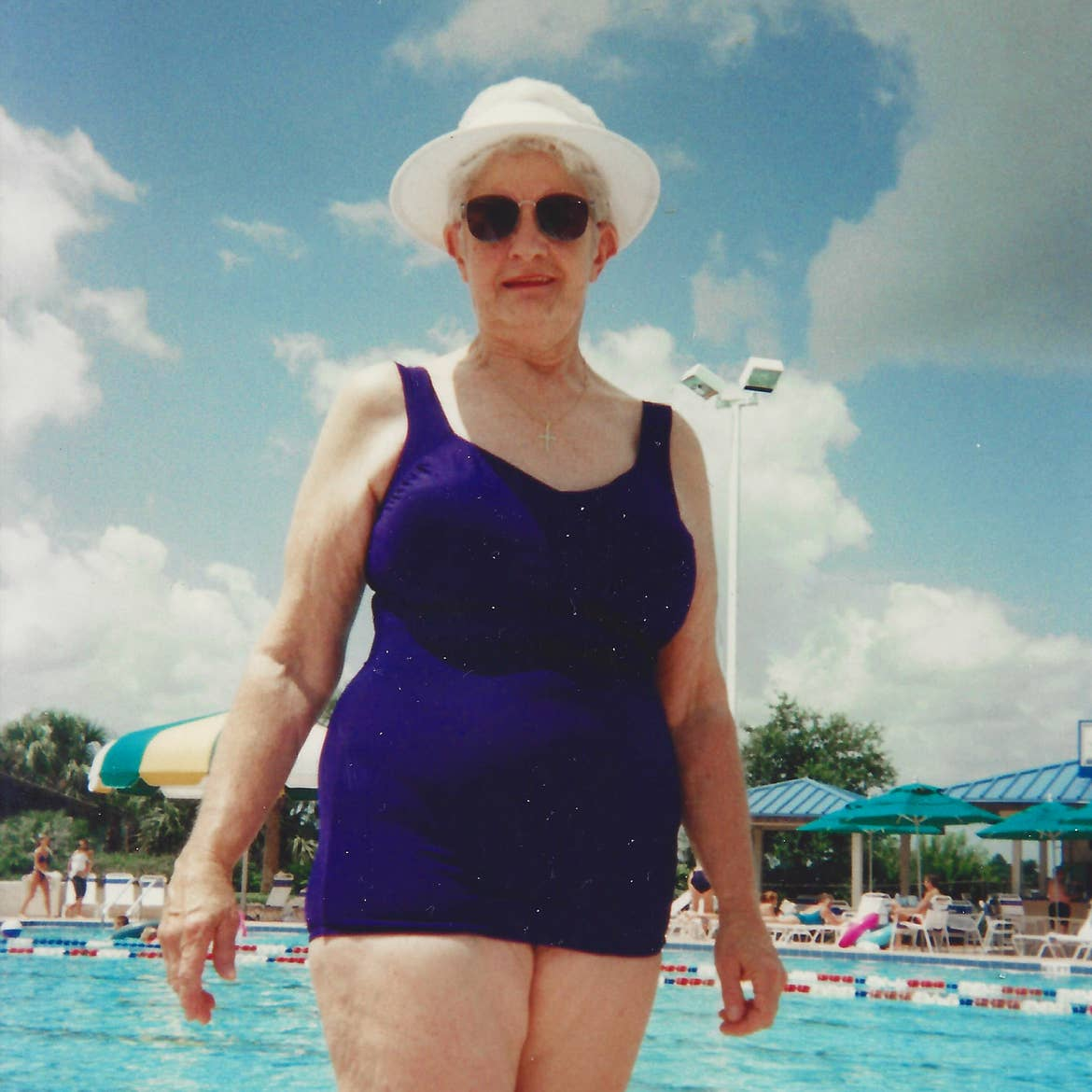 An older caucasian woman stands under a blue sky wearing a blue swimsuit and white sunhat.