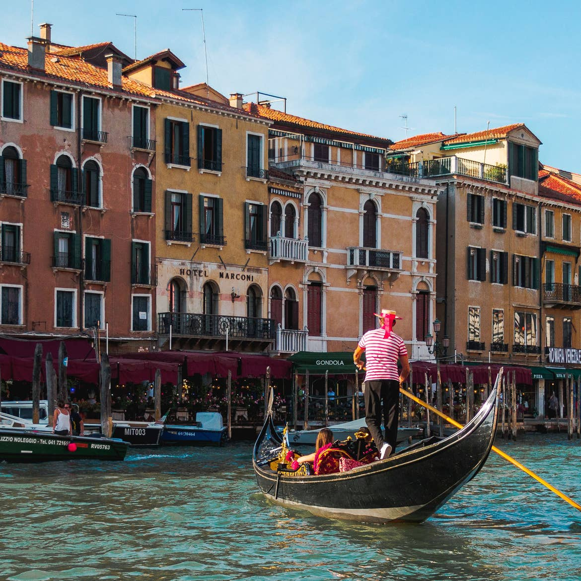 A Gondolier wearing a straw hat and striped red and white shirt paddles guests along the river in Venice, Italy.