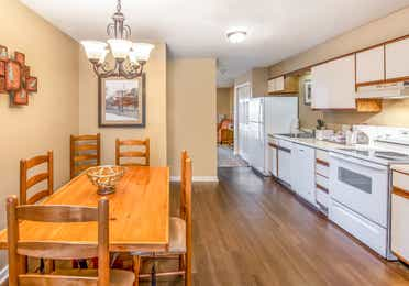 A kitchen and dining table in a one bedroom villa at Oak n' Spruce Resort in South Lee, Massachusetts
