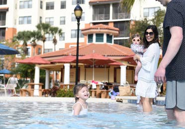 Family standing in the shallow end of a pool.