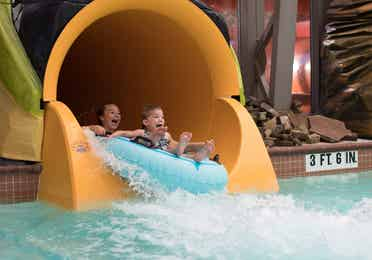 Two young girls on an inner tube coming down the bottom of a large water slide at Orange Lake Resort in Orlando, FL