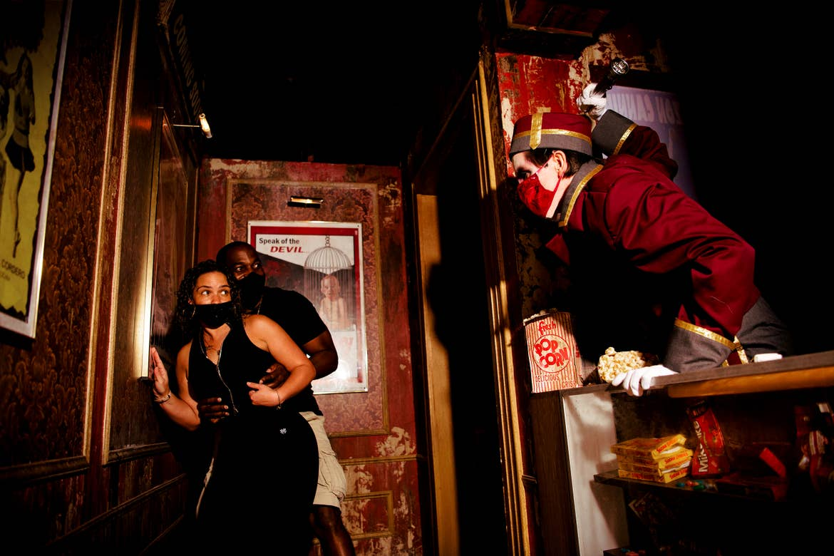 A man and woman hide from a horror nights performer in a Haunted House.