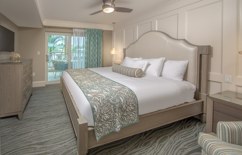 Bedroom with king bed and access to a furnished balcony in a two-bedroom Signature villa at Cape Canaveral Beach Resort