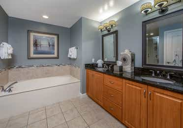 Bathroom with large bathtub and double sinks with two mirrors in a three-bedroom villa at Sunset Cove Resort in Marco Island, Florida