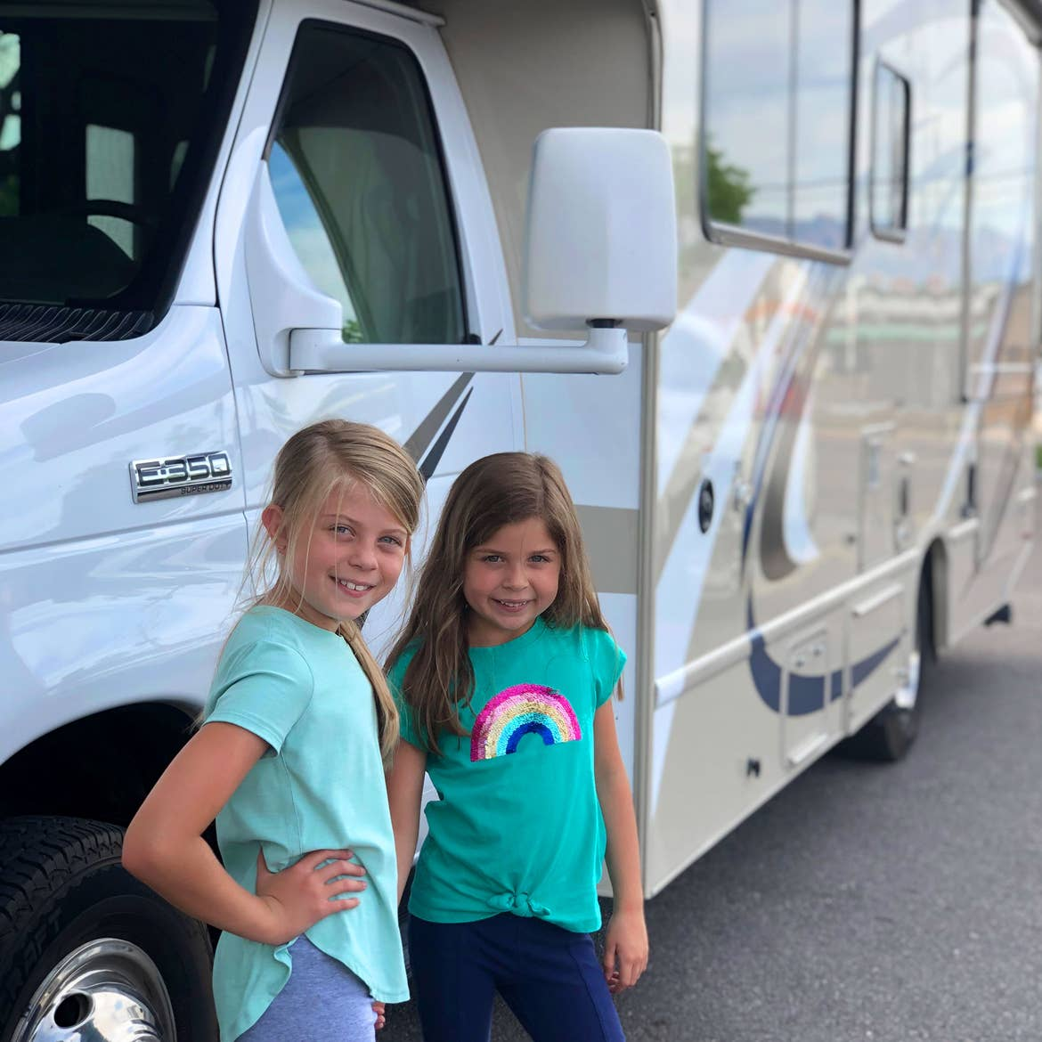 Author, Chris Johnstons' daughters, Kyndall (left), and Kyler (right) pose with in front of a white RV.