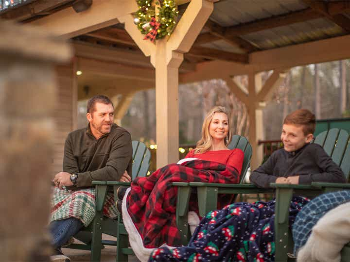 Family of three under blankets surrounded by festive holiday decor outdoors.