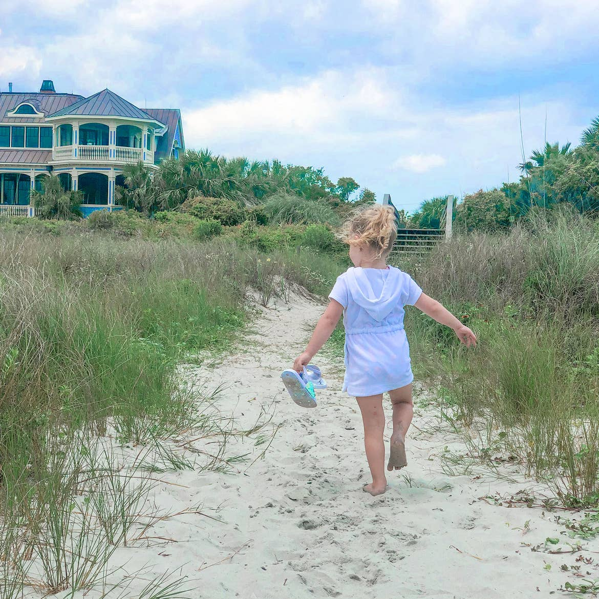 Featured Contributor, Brianna Steele's daughter walks barefoot in the sands towards a beach house in the distance.