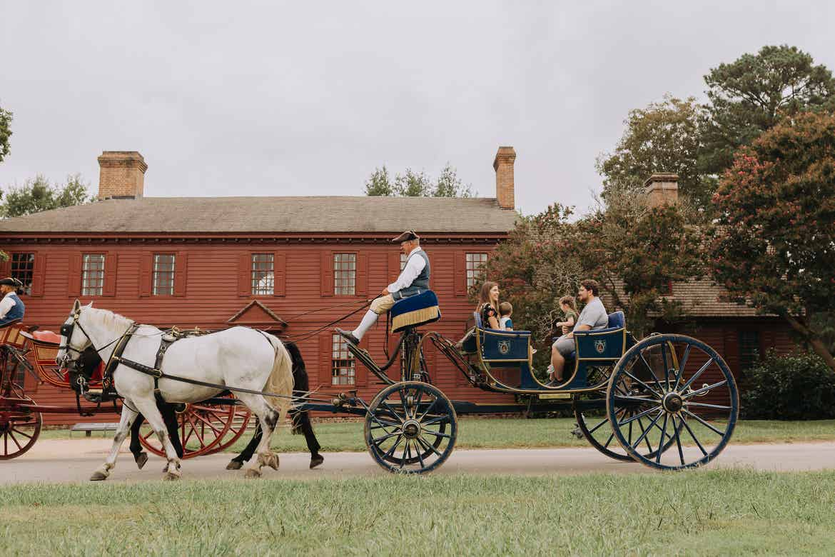 A family sits on a horse-drawn carriage driven by an actor wearing period-appropriate attire at Colonial Williamsburg in Williamsburg, Virginia.