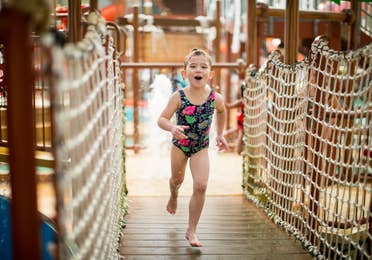 Toddler girl running on a bridge through the splash zone at the Waterpark at the Villages