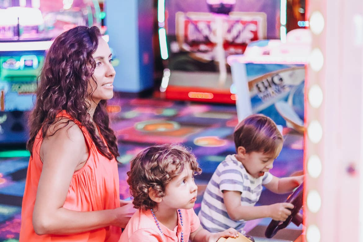 Raff's wife and two kids playing video games at the arcade.