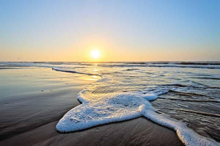 Wave crashing onto beach during sunset