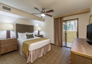 Guest bedroom with balcony access and flat screen TV in a three-bedroom villa at Scottsdale Resort