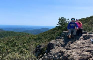 Featured Contributor, Ashley Fraboni (right) and Fiancé, Nicholas (left) sit atop a rock a Shenandoah National Park.