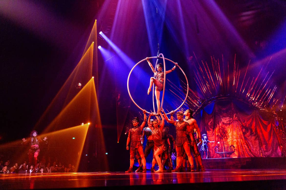Several Cirque Du Soleil performers hold a woman in two hoops while standing onstage with blue, yellow and red stage lighting upon them.