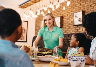 Waitress bringing food to a table of restaurant guests.