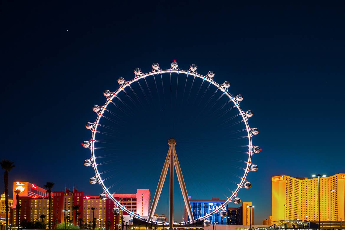The 'High Roller' ferris wheel stands illuminated in front of a dark blue night sky and surrounding buildings on the Las Vegas strip.