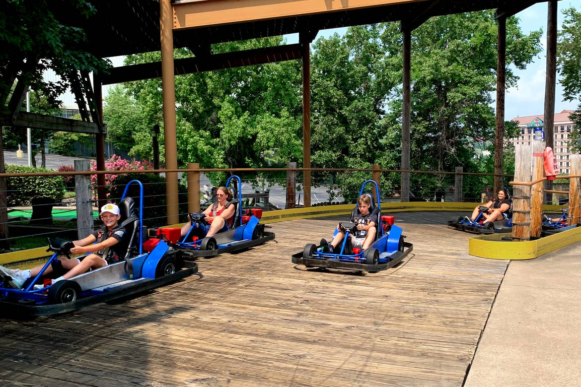 Two boys and two women ride blue go karts on a track.