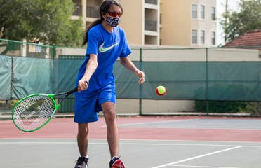 Special Olympic Athlete, Roan Luallen, plays tennis wearing a blue t-shirt and shorts with a safety mask and sunglasses on the courts of our Orange Lake Resort located in Orlando, Florida.