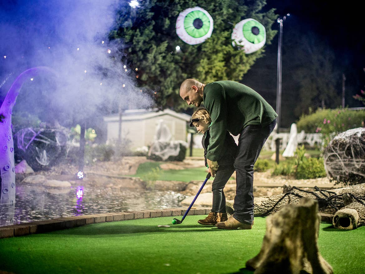 A man and young girl play mini-golf at night.