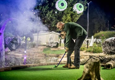 Father and child playing ghostly mini golf.