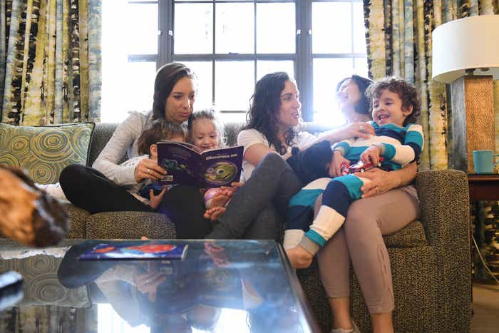 Raff's family reading on the couch in villa