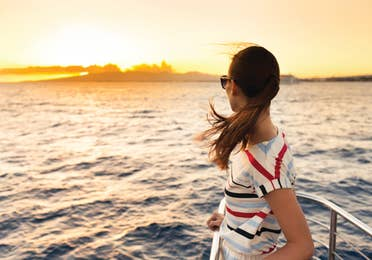 Woman standing on yacht looking out into the sunset