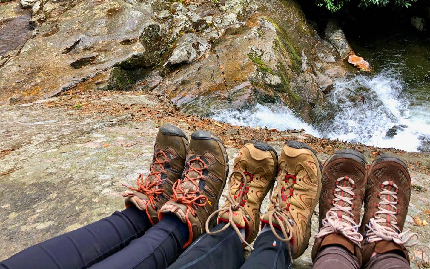 Featured Contributor, Jennifer C. Harmon (left) and her two girlfriends wear hiking boots as their feet sit near the top of a waterfall.