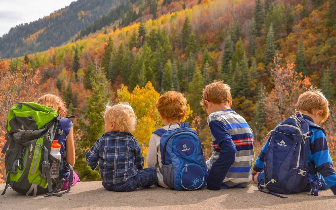 several children sit on a cliff overlooking fall foliage in the mountains.