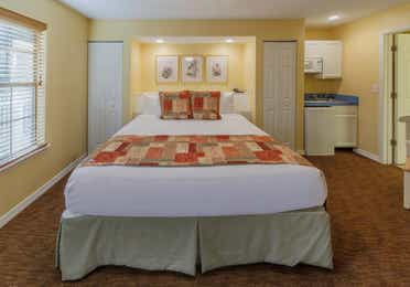 Bedroom with king bed and kitchenette in a presidential two bedroom villa at Piney Shores Resort in Conroe, Texas