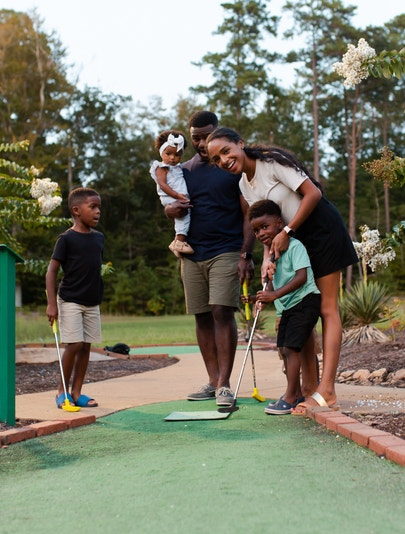 Mother teaching son how to putt at a miniature golf course at Holiday Inn Club Vacations Williamsburg Resort