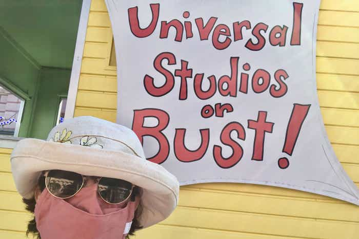 Author, Rona, stands in front of a yellow building with the sign, 'Universal Studios or Bust!'