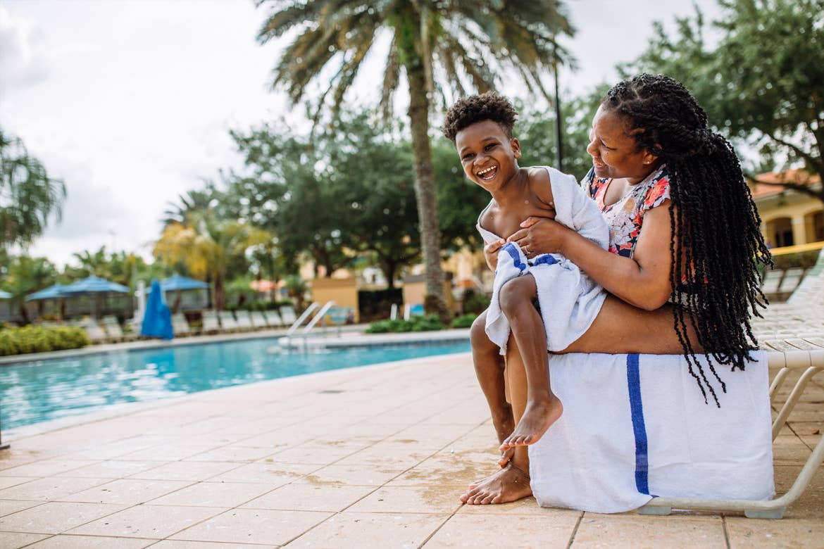 Krystin Godfrey (right) helps her son, Joshua (left) dry off poolside in River Island at our Orange Lake Resort located in Orlando, FL.