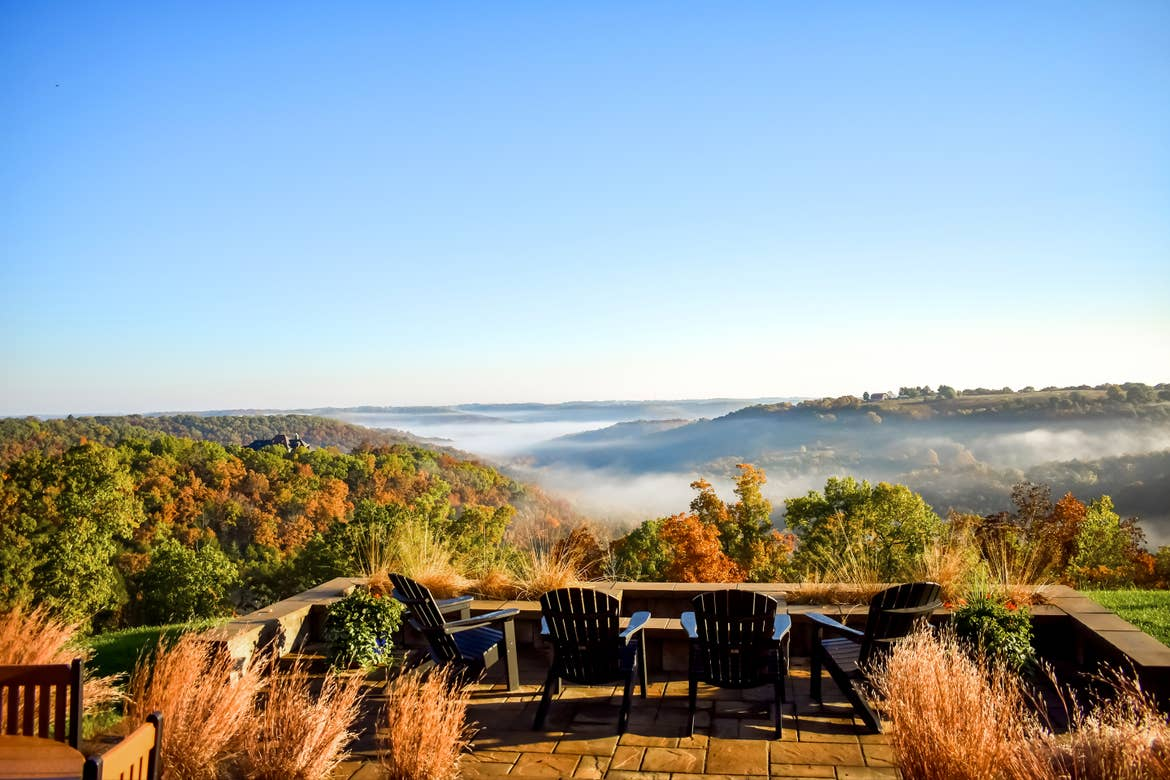 Several Adirondack chairs overlook fall foliage in Branson, MO.
