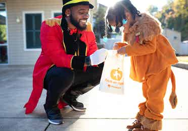 Man dressed as a Ringmaster handing candy to a girl dressed as a lion during a Fall event