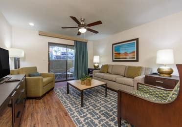 Living room area with couch, two chairs and a flat screen TV in a two-bedroom villa at Scottsdale Resort