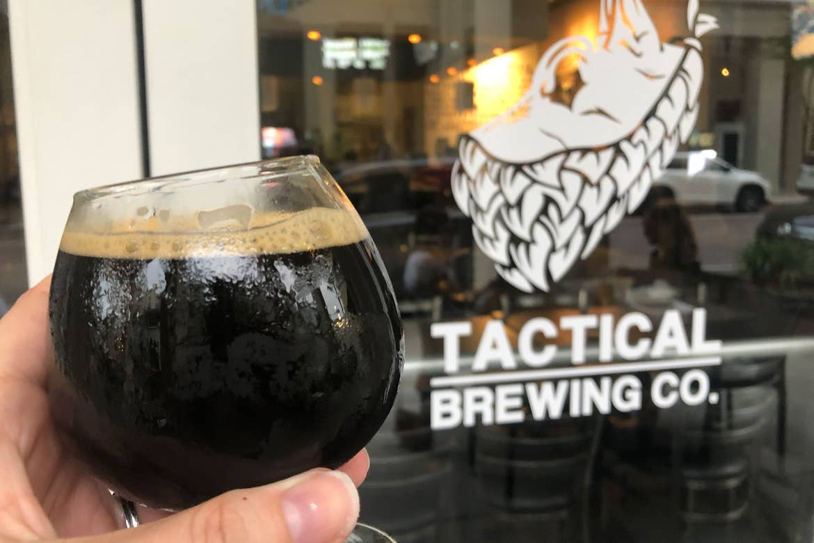 A hand holds a stemmed stout glass in front of the exterior door decal of 'Tactical Brewing Co.'