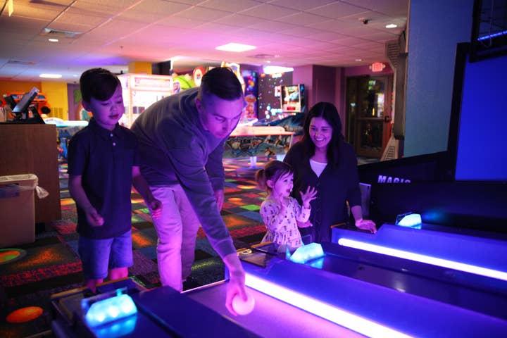 Family playing ski-ball in arcade at Orange Lake Resort near Orlando, Florida
