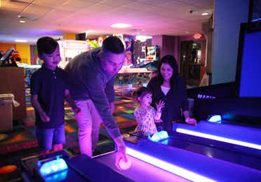 Family playing ski-ball in arcade at Orange Lake Resort near Orlando, Florida