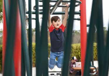 Young boy on monkey bars at Orange Lake Resort near Orlando, Florida