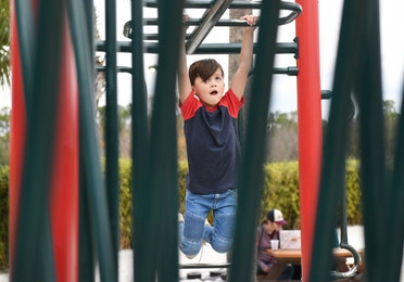 Young boy on monkey bars at Orange Lake Resort near Orlando, Florida