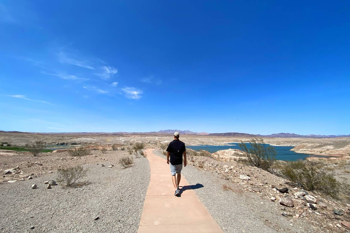 A caucasian man wearing a white hat, black t-shirt, and denim shorts walks on a path at the Lake Mead National Recreation Area under a blue, lightly-clouded sky.