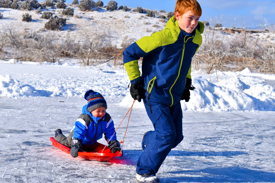 Featured Contributor, Jessica Averett's sons wear winter gear in the snow as the oldest (right) pulls the youngest (left) on a sled.
