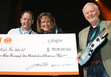 Tom Nelson, HCV CEO, presenting an oversized check to Give Kids the World