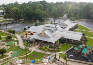Aerial shot of Grill and Activity Center buildings surrounded by playground and mini golf course at Villages Resort in Flint, Texas.