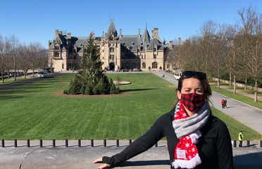 Author, Jenn C. Harmon, stands in front of the Biltmore Estate wearing a buffalo plaid red and black face mask and festive scarf over a black jacket.