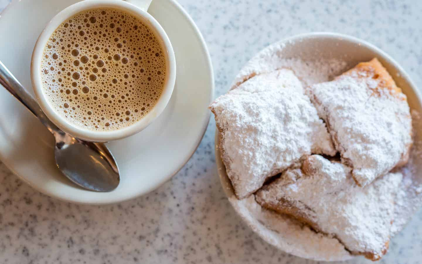 Beignets placed on a table with some coffee on white plates.