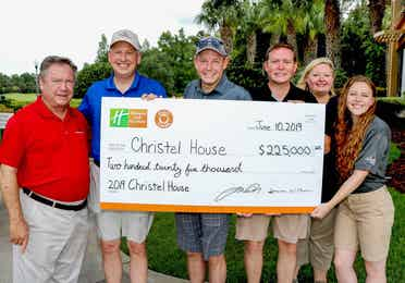 Group of people holding a large presentation check for $225,000 made payable to Christel House